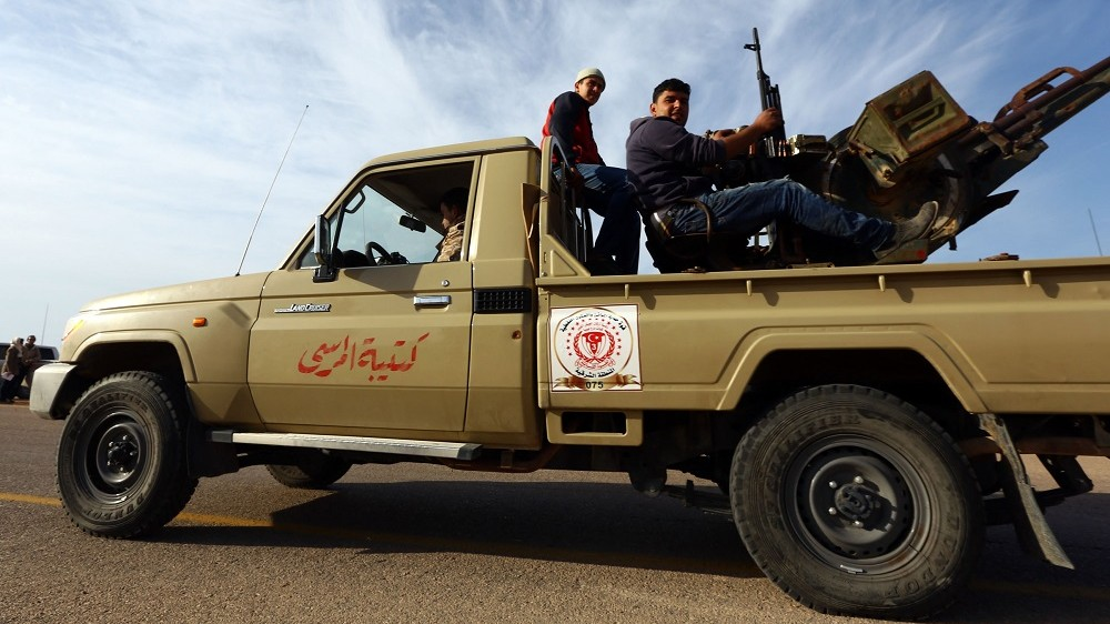 Members of a brigade loyal to the Fajr Libya (Libya Dawn), an alliance of Islamist-backed militias, sit on a pick up truck mounted with a machine gun on March 15, 2015 in Libya's coastal city of Sirte, which lies 500 kilometres (310 miles) east of the capital, Tripoli. Rare clashes between fighters from the Islamic State group and Fajr Libya erupted on March 14, 2014 in Sirte, security and militia officials said, a month after Fajr Libya said it had sent reinforcements to the city to restore security.   AFP PHOTO / MAHMUD TURKIA / AFP PHOTO / MAHMUD TURKIA