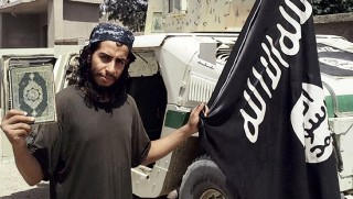 """An undated picture taken on November 16, 2015 from the February 2015 issue 7 of the Islamic State (IS) group online English-language magazine Dabiq, purportedly shows 27-year-old Belgian IS group leading militant Abdelhamid Abaaoud, also known as Abu Umar al-Baljiki and believed to be the mastermind of a jihadist cell dismantled in Belgium in January 2015, posing at an undisclosed location to illustrate an interview he gave to the magazine, claiming to have rejoined the extremist group in Syria. Flemish-language newspaper De Standaard reported that Brahim Abdeslam, one of the attackers who blew himself up during the Paris attacks last week, had links to Abaaoud, a Belgian of Moroccan descent who allegedly fought with the IS jihadist group in Syria and remains at large.  AFP PHOTO / HO / DABIQ === RESTRICTED TO EDITORIAL USE - MANDATORY CREDIT """"AFP PHOTO / HO / DABIQ"""" - NO MARKETING NO ADVERTISING CAMPAIGNS - DISTRIBUTED AS A SERVICE TO CLIENTS FROM ALTERNATIVE SOURCES, AFP IS NOT RESPONSIBLE FOR ANY DIGITAL ALTERATIONS TO THE PICTURE'S EDITORIAL CONTENT, DATE AND LOCATION WHICH CANNOT BE INDEPENDENTLY VERIFIED === / AFP PHOTO / DABIQ / -"""
