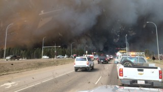 CANADA, Fort McMurray: Heavy smoke rises above Alberta Highway 63, near Fort McMurray, Alberta, southern Canada, as a huge wildfire has forced the evacuation of the entire population of the Canadian city, on May 3, 2016. The evacuation from Fort McMurray is the biggest in Alberta's history. - Joshua Brophy
