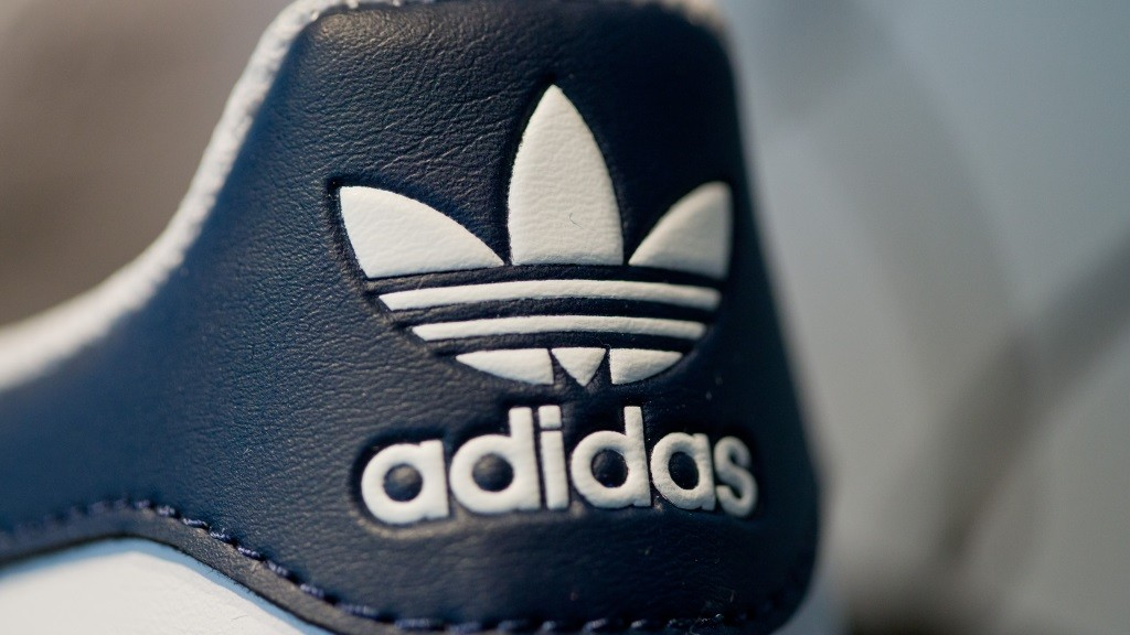The logo of sportwear company Adidas AG can be seen on a shoe during the company's balance sheet press conference in Herzogenaurach, Germany, 03 March 2016. Photo: DANIEL KARMANN/dpa