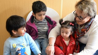 Ilka Fischer, employee of the medical station, looks after children from Syria while their mother is examined by a midwife in the Neue Messe refugee reception facility in Leipzig,Germany, 14 March 2016. The Neue Messe reception facility is currently home to 520 asylum seekers. Photo: WALTRAUDGRUBITZSCH/dpa