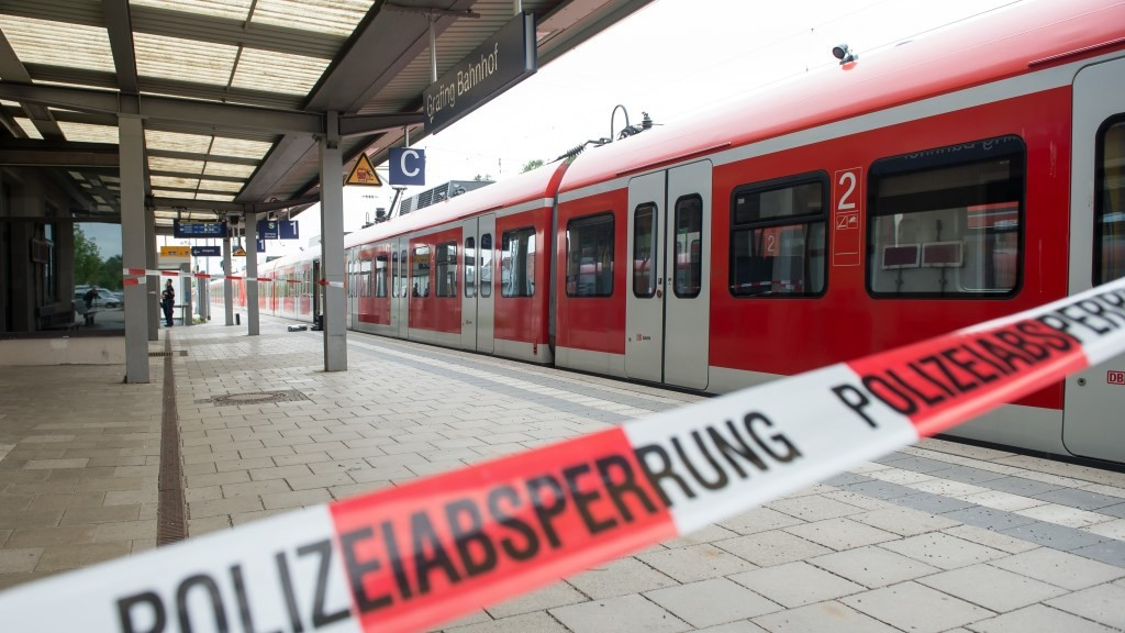 GRAFING, GERMANY - MAY 10 : A police line of the German police is seen in front of a train at the crime scene after a deadly knife attack on May 10, 2016 in Grafing near Munich, Germany. One person has died and three others have been injured after a man launched a knife attack at Grafing commuter train station. Lukas Barth / Anadolu Agency