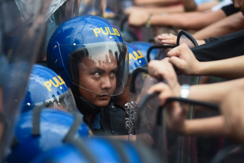 """MANILA, PHILIPPINES - NOVEMBER 18: Riot police struggle to contain protesters as members of the student group """"League of Filipino Students"""" attempt to march towards the Philippine International Convention Center (PICC), the venue of the Asia Pacific Economic Cooperation (APEC) Summit in Pasay City, 18 November 2015. Heightened security measures are implemented in the capital as leaders of different nations take part in the international conference. George Calvelo / Anadolu Agency"""