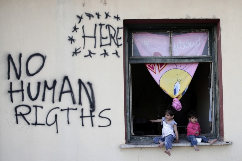 IDOMENI, GREECE - MAY 19: Two refugee children sit on the corner of a window as they try to continue their daily life at Idomeni refugee camp in Greece on May 19, 2016. Ayhan Mehmet / Anadolu Agency