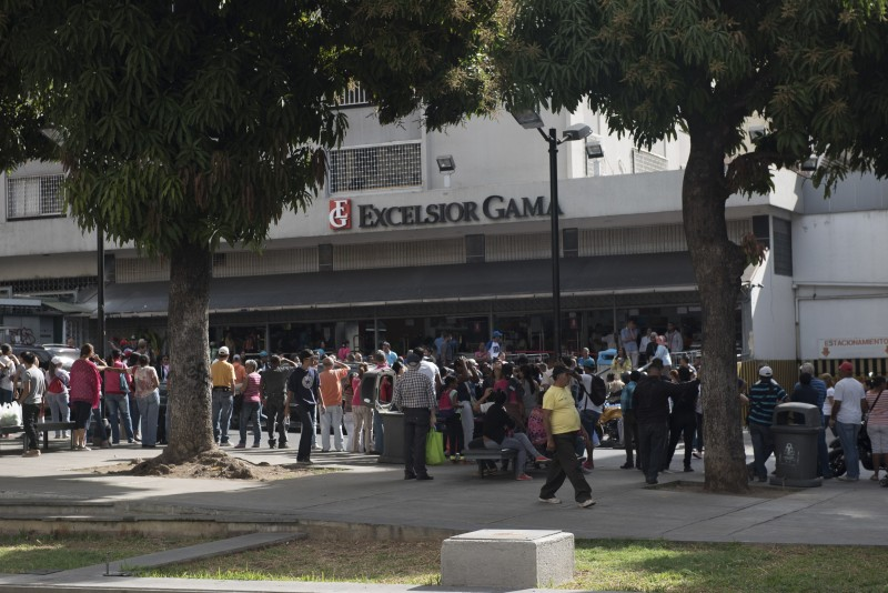 CARACAS, VENEZUELA - FEBRUARY 27: People line up to buy basic products outside a supermarket in Caracas, Venezuela on February 27, 2016. Venezuela suffers from the shortage of food, medicines, household goods and personal hygiene products for several years.    Carlos Becerra / Anadolu Agency