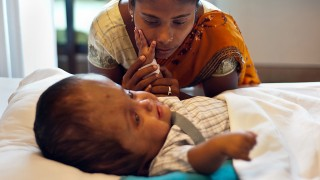 Fatima Khatun comforts her twenty-two month old daughter, Indian patient Roona Begum, prior to Roona's surgery at a hospital in Gurgaon on the outskirts of New Delhi on November 29, 2013. Roona, whose plight captured international sympathy, has battled through several life-saving surgical procedures which saw doctors at a hospital drain fluid from her head and dramatically reduce the size of her skull. AFP PHOTO/MANAN VATSYAYANA / AFP PHOTO / MANAN VATSYAYANA