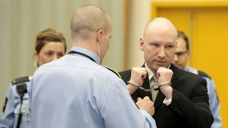 Norwegian mass killer Anders Behring Breivik (R) has his handcuffs removed inside the court room in Skien prison, March 16, 2016.Behring Breivik is charging Norwegian authorities of violating his human rights by holding him in isolation for almost five years. / AFP PHOTO / NTB Scanpix / Lise Aserud / Norway OUT