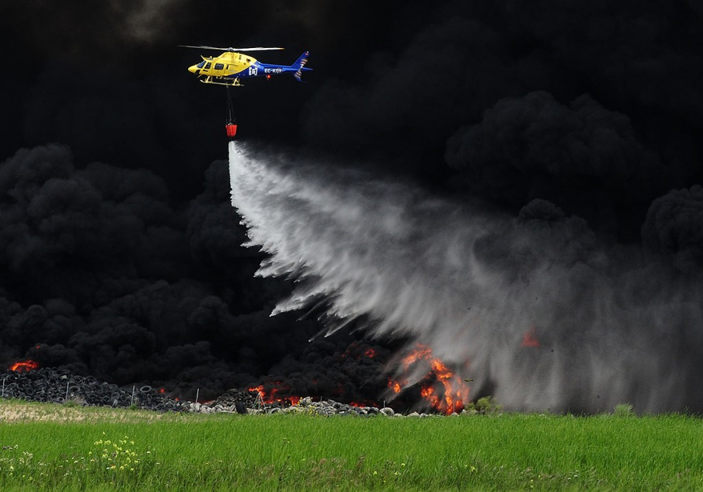 SESENA NUEVO, SPAIN - MAY 13:  A helicopter drops water onto burning tyres at an illegal dump on May 13, 2016 in Sesena Nuevo, Spain. The dump, which stored over 75.000 tonnes of used rubber tyres was declared illegal in 2003 but both the Regional Government of Madrid and Castilla La Mancha were unable to come to an agreement as to who would pay for the estimated 4 million euro clean-up and removal of the dump.  (Photo by Denis Doyle/Getty Images)