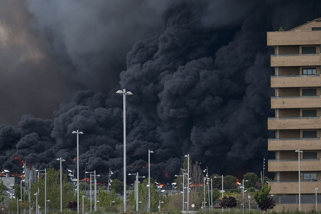 Black clouds of smoke are produced by tyres burning in an uncontrolled dump near the town of Sesena, after a fire brokeout early on May 13, 2016.A huge waste ground near Madrid where millions of tyres have been dumped was on fire today, releasing a thick black cloud of toxic fumes that officials worry could harm residents nearby. / AFP PHOTO / PEDRO ARMESTRE