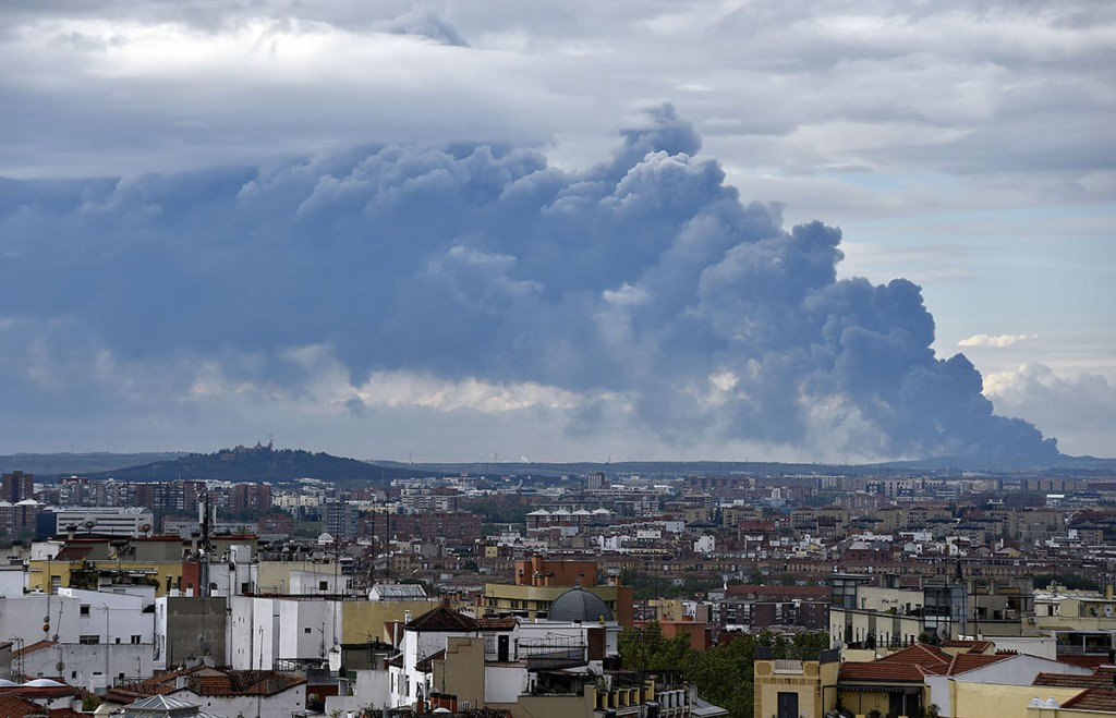 Picture taken from the Almudena cathedral in Madrid shows a huge smoke column caused by a fire in an uncontrolled dump near the town of Sesena, on May 13, 2016.A huge waste ground near Madrid where millions of tyres have been dumped was on fire today, releasing a thick black cloud of toxic fumes that officials worry could harm residents nearby. / AFP PHOTO / GERARD JULIEN