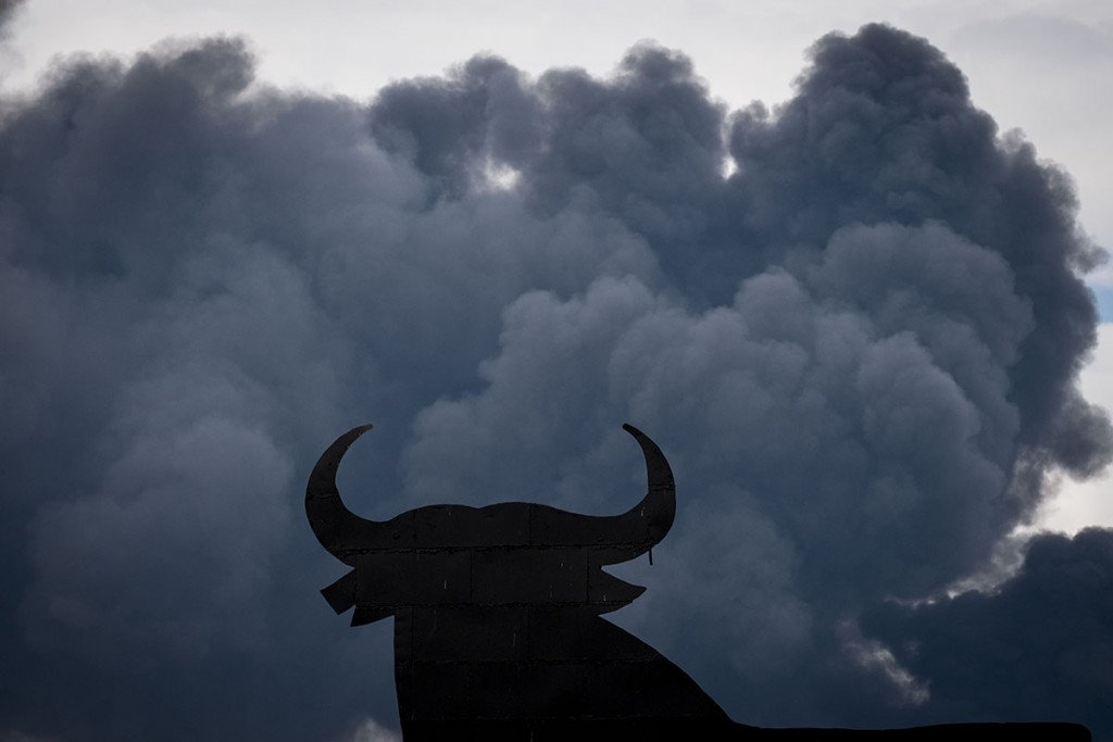 """The shape of an """"Osborne Bull"""" is pictured with black clouds of smoke on the background,  produced by tyres burning in an uncontrolled dump near the town of Sesena, after a fire brokeout early on May 13, 2016.A huge waste ground near Madrid where millions of tyres have been dumped was on fire today, releasing a thick black cloud of toxic fumes that officials worry could harm residents nearby. / AFP PHOTO / PEDRO ARMESTRE"""