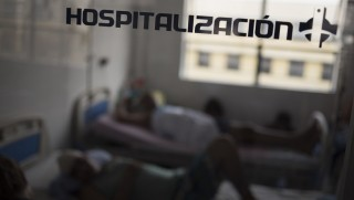 Patients lie on beds in a hospital in Barquisimeto, Venezuela, on Monday, Feb. 22, 2016. In Barquisimeto, the hub of Venezuela's farming heartland, shoppers line up for food, neighborhoods are dark from rolling blackouts and hospitals so crowded that the sick sometimes share beds. Photographer: Carlos Becerra/Bloomberg via Getty Images