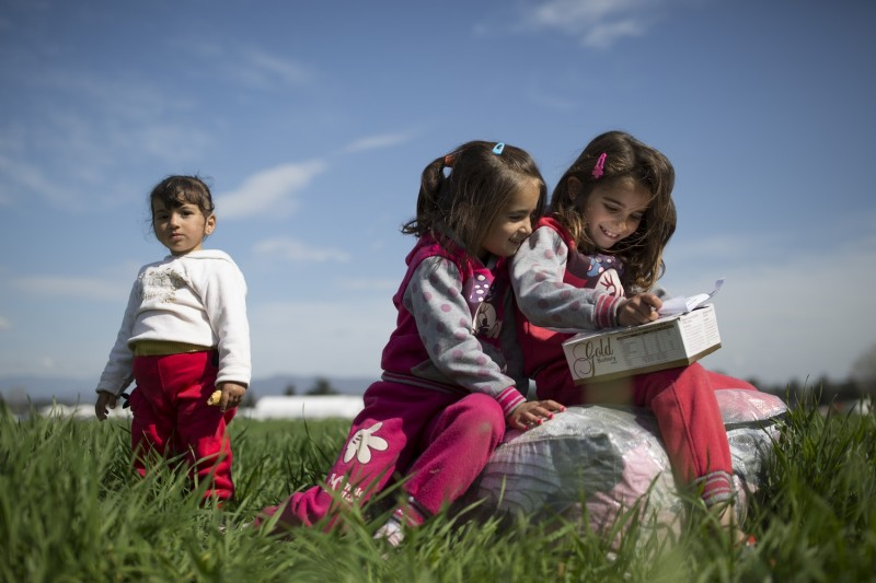IDOMENI, GREECE - MARCH 06:  (L-R) Ruhiv, 2, Inas, 7 and Kulistan, 8, from Al-Hasakah in Syria relax in a field near a refugee camp at the Greek-Macedonia border on March 06, 2016 in Idomeni, Greece. Doctors are warning that conditions at the camp are becoming dangerous for children, with medics dealing with a range of illnesses, including hypothermia. The transit camp at the border is becoming increasingly overcrowded as thousands of refugees continue to arrive from Athens and the Greek Islands. Macedonia's border with Greece remains 'open' but after allowing 580 refugees a day to cross into the country at the beginning of the week, the numbers passing have fallen dramatically with only a handful every day. According to local authorities approximately 12,000 refugees and migrants now remain stuck at the border as they wait to enter Macedonia to continue their journey North into Western Europe.  (Photo by Dan Kitwood/Getty Images)