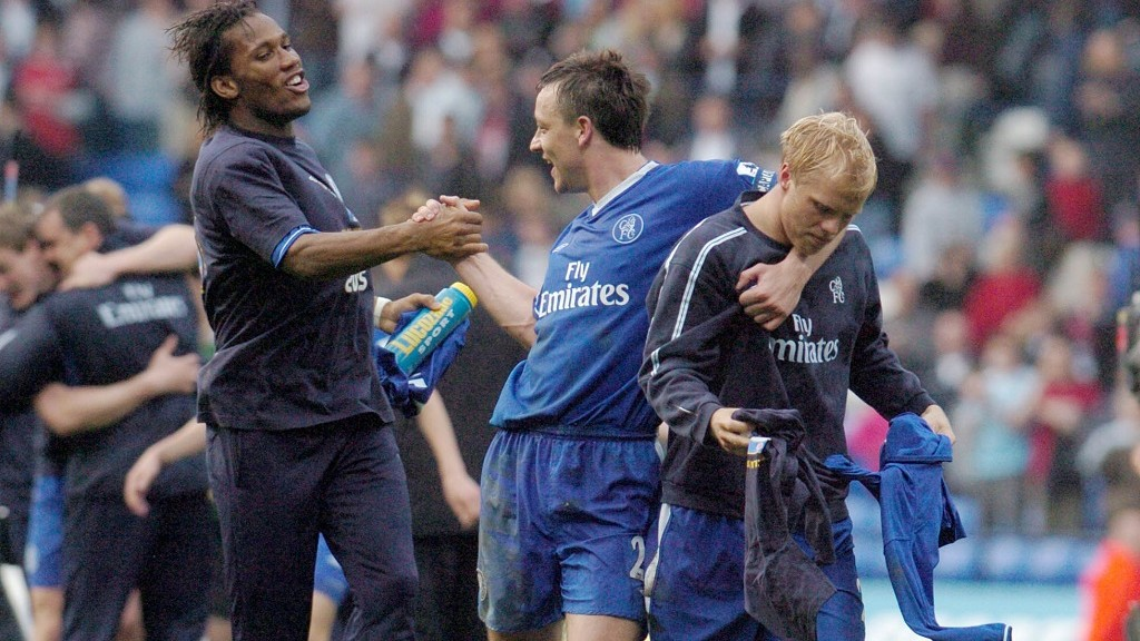 Chelsea's Ivorian striker Didier Drogba (L) salutes captain John Terry and Eidur Gudjohnssen after Chelsea's 2-0 victory against Bolton, giving them the Premiership title, at the Reebok Stadium, in Bolton, 30 April 2005. AFP PHOTO PAUL BARKER - No telecos, website uses subject to subscription of a license with FAPL on www.faplweb.com / AFP PHOTO / PAUL BARKER
