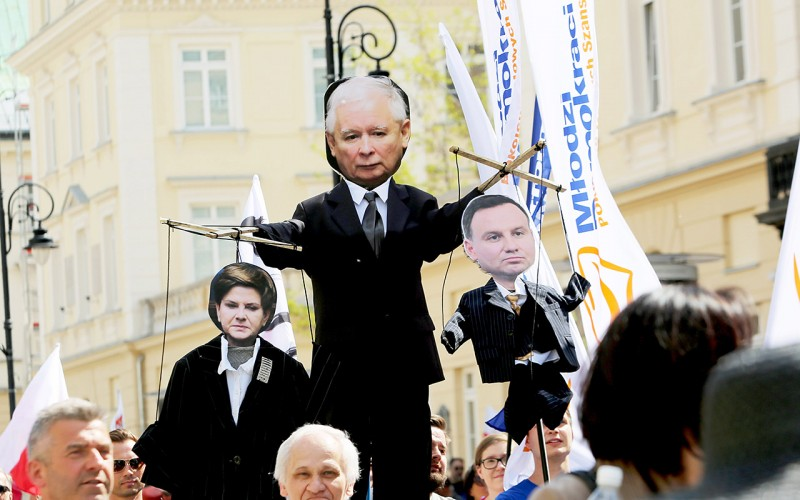 """WARSAW, POLAND - 2016/05/07: An effigy of the leader of the Law & Justice Party (PiS), Jaroslaw Kaczynski holding Premier Beato Szydlo and Polish President Andrzej Duda as puppets is seen during a massive protest in Warsaw, Poland. Several hundred thousand people gathered for a demonstration organized by the Committee to Protect Democracy (KOD) and the political opposition parties in Warsaw, Poland on May 07 2016. The slogan of the protest was, """"We are and we will be in Europe"""" (Jestemy i bdziemy w Europie) The protest was a response to recent political overtures by politicians in the ruling government, the Law and Justice Party, that Poland may be planning to exit the European Union. Opposition parties in Poland's parliament, including the Civic Platform Party (PO), the Modern Party (.Nowoczesna) as well as the Polish Peasant Party (PSL), the Green Party, and the Polish Teacher's Union were among the political representatives in the demonstration. The demonstration took place two days before May 9, which is celebrated as Europe day across the European Union as a victory peace and unity in Europe. (Photo by Anna Ferensowicz/Pacific Press/LightRocket via Getty Images)"""