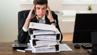 Stressed Young Businessman Looking At Stack Of Folders In Office