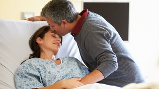 Loving Affectionate Husband Visiting Wife In Hospital