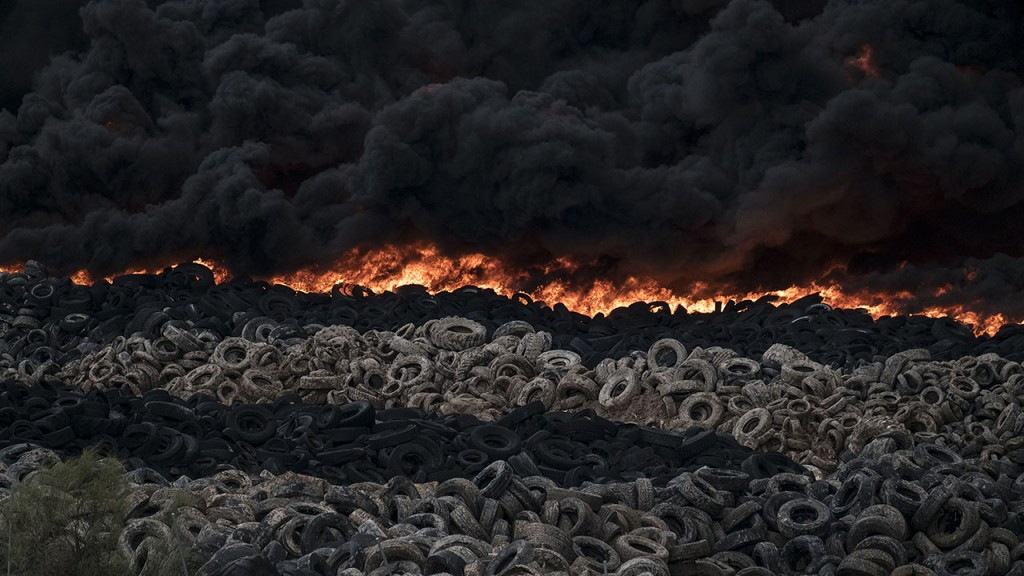 Tyres burn in an uncontrolled dump near the town of Sesena, after a fire brokeout early on May 13, 2016.A huge waste ground near Madrid where millions of tyres have been dumped was on fire today, releasing a thick black cloud of toxic fumes that officials worry could harm residents nearby. / AFP PHOTO / PEDRO ARMESTRE