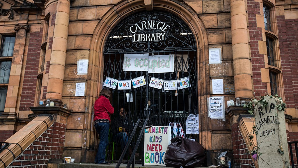 """LONDON, ENGLAND - APRIL 04:  A woman chats with a friend who is part of a group occupying Carnegie Library on April 4, 2016 in London, England. The building has been occupied by members of the local community angered at Lambeth Council plans to close the library and reopen it as a service providing """"fitness centres alongside some library services"""". Library campaigners have accused the government of """"hiding"""" the scale of cuts which they claim will force the closure of around 400 UK libraries by 2016, bringing the total of library closures since 2009 to more than 1,000.  (Photo by Carl Court/Getty Images)"""
