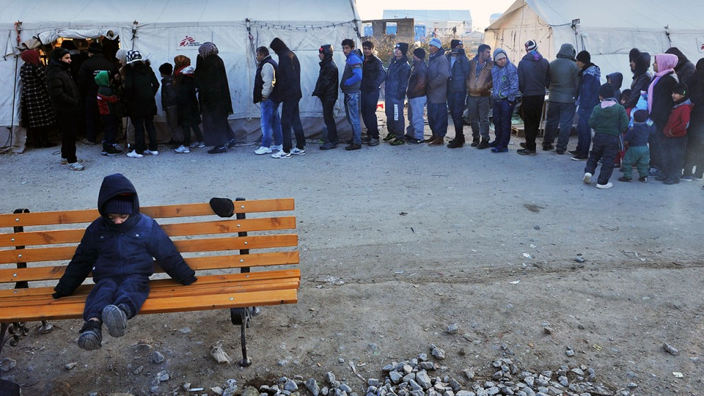 """Migrants and refugees queue to receive clothes as they wait to cross the border from Greece to Macedonia near Idomeni, on January 21, 2016. Some 2,000 migrants began crossing into Macedonia on January 21 in freezing temperatures as the country conditionally reopened its border with Greece after closing it temporarily. """"The border crossing for migrants near (Macedonian border town) Gevgelija opened early this morning, but only those migrants whose Greek registration papers show their final destination as Germany or Austria can enter,"""" a senior police official in Skopje told AFP.  / AFP PHOTO / SAKIS MITROLIDIS"""