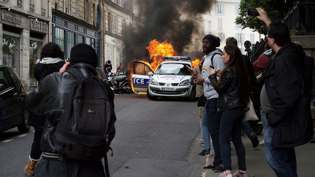 """People stand by a police car burning after being set on fire during an unauthorized counter-demonstration against police violence on May 18, 2016 in Paris, as Police across France demonstrate today against the """"anti-cop hatred"""" they say they have endured during a wave of anti-government protests since early March.Some 350 members of the security forces have been injured during the protests against the labour reforms, including one who lost the use of an eye. / AFP PHOTO / CYRIELLE SICARD"""