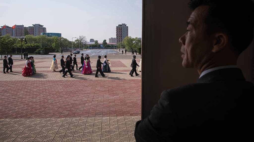 A government guide watches as attendees of the 7th Workers Party Congress arrive for a cultural performance in Pyongyang on May 11, 2016. North Korea's rare ruling party congress was seen as a chance for young leader Kim Jong-Un to bolster his power, some four years after succeeding his late father. / AFP PHOTO / Ed Jones