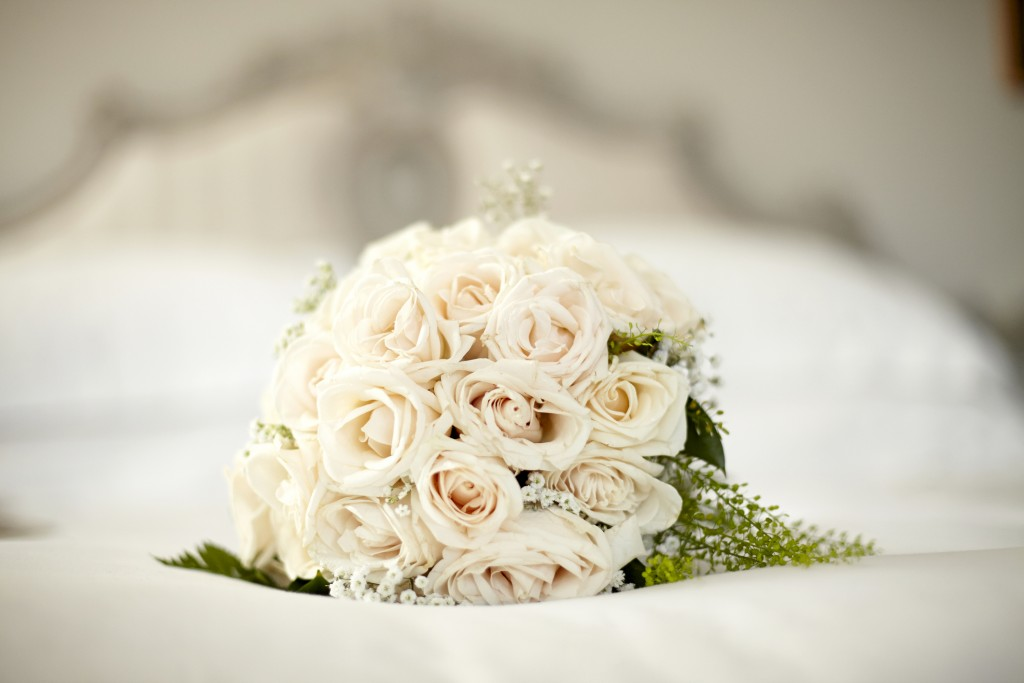 Bouquet with white roses lying on a bed. Horizontal format. Shot with Canon EOS 5D.