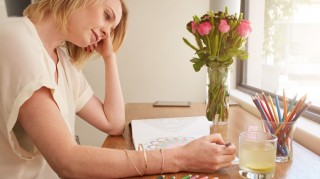 Woman relaxing at home by coloring book