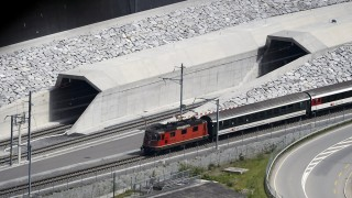 A train makes its way at the north entrance of the new Gotthard Base Tunnel the world's longest train tunnel on the eve of its opening ceremony on May 31, 2016 in Erstfeld.  The new Gotthard Base Tunnel (GBT) is set to become the world's longest railway tunnel when it opens on June 1.The 57-kilometre (35.4-mile) tunnel, which runs under the Alps, was first conceived in sketch-form in 1947 but construction began 17 years ago. / AFP PHOTO / FABRICE COFFRINI