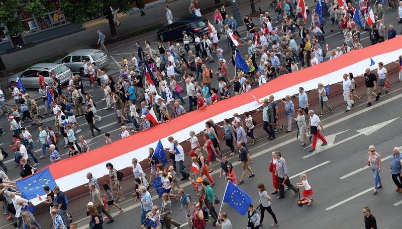 People carry a Polish national flag as they march to protest the policies of the right-wing Law and Justice government, on the 27th anniversary of the partly free elections that led to overthrowing communism, during a demonstration organized  by the Committee for the Defense of Democracy (KOD) movement in Warsaw on June 4, 2016.  / AFP PHOTO / JANEK SKARZYNSKI