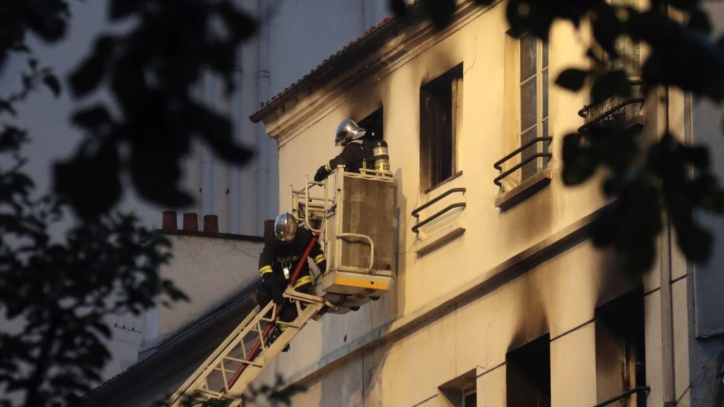 Firemen stand in an aerial bucket to extinguish a fire in a building on June 6, 2016 in Saint-Denis, near Paris. A fire broke out on June 6, 2016 evening in a residential building in central Saint-Denis, causing seven wounded, two seriously, according to concordant sources. / AFP PHOTO / Jacques DEMARTHON