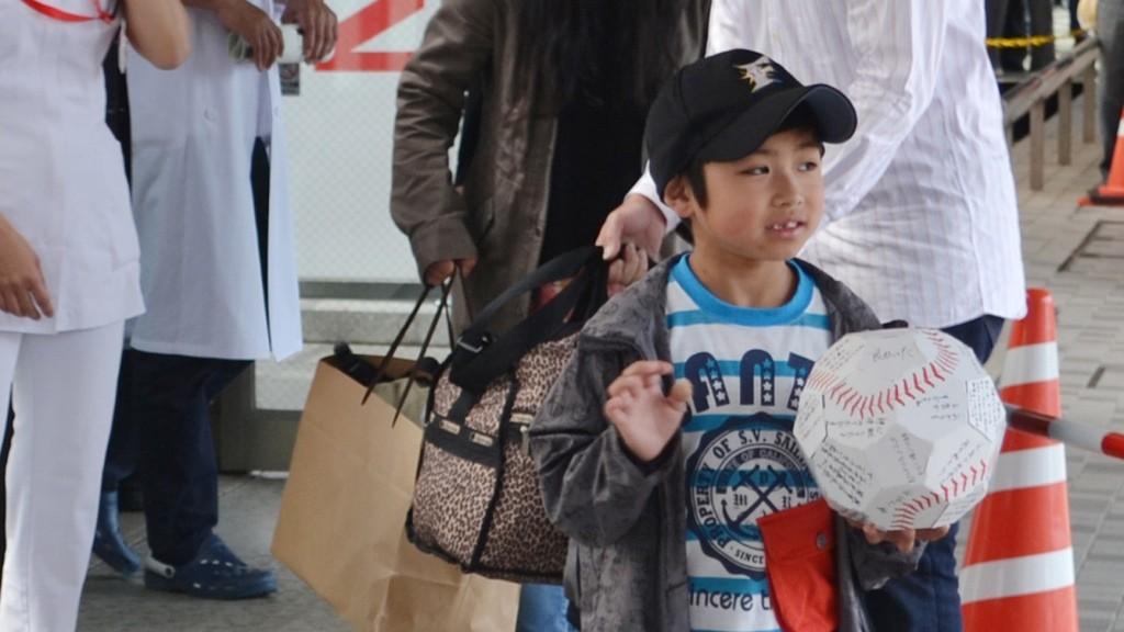 Yamato Tanooka (front) waves to photographers in front of his father, Takayuki (R) as he leaves the Hakodate Municipal Hospital in Hakodate city, Hokkaido prefecture on June 7, 2016.   A seven-year-old boy who survived for nearly a week after being abandoned by his parents in a forest left hospital on June 7, capping a 10-day drama that captivated Japan and sparked a national conversation about child discipline. / AFP PHOTO / JIJI PRESS / JIJI PRESS / Japan OUT
