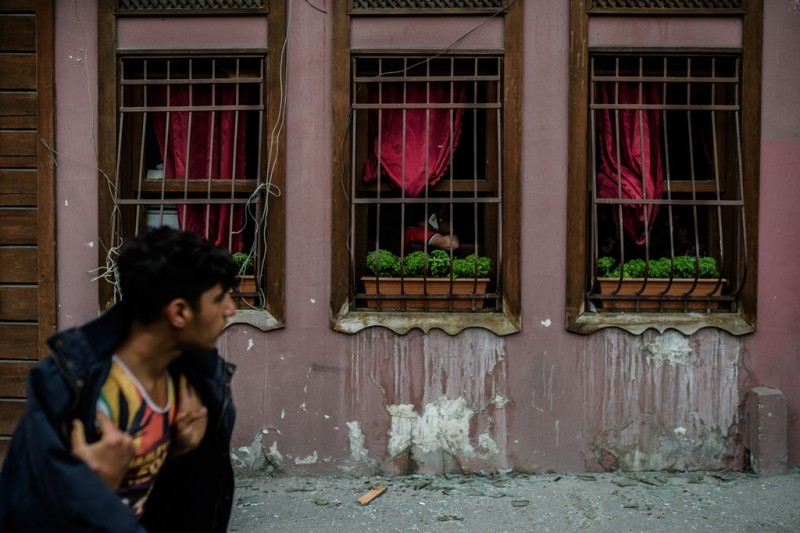 A man walks past a building with broken windows due to the explosion of a bomb attack that targeted a bus shuttle service carrying anti-riot police in the Vezneciler district of Istanbul on June 7, 2016. A bomb ripped through a Turkish police bus near Istanbul's historic centre, killing seven officers and four civilians in the latest of a string of attacks in Turkey's biggest city. / AFP PHOTO / OZAN KOSE