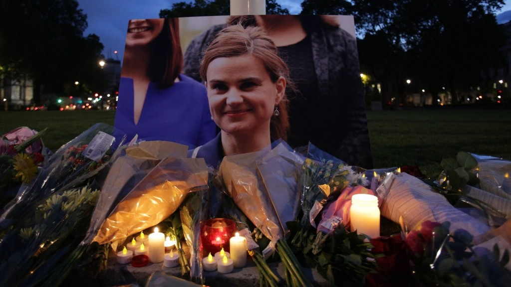Floral tributes and candles are placed by a picture of slain Labour MP Jo Cox at a vigil in Parliament square in London on June 16, 2016. Cox died today after a shock daylight street attack, throwing campaigning for the referendum on Britain's membership of the European Union into disarray just a week before the crucial vote.  / AFP PHOTO / DANIEL LEAL-OLIVAS