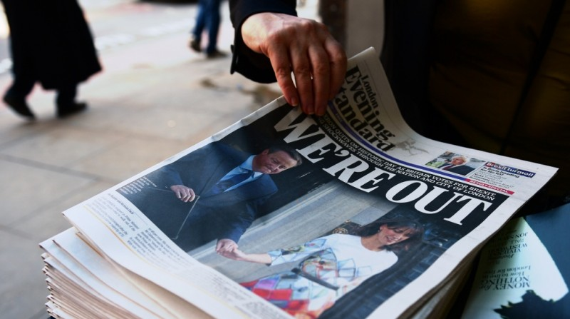 A woman takes a copy of the London Evening Standard with the front page reporting the resignation of British Prime Minister David Cameron and the vote to leave the EU in a referendum, showing a pictured of Cameron holding hands with his wife Samantha as they come out from 10 Downing Street, in London on June 24, 2016.  Britain voted to break away from the European Union on June 24, toppling Prime Minister David Cameron and dealing a thunderous blow to the 60-year-old bloc that sent world markets plunging. / AFP PHOTO / LEON NEAL