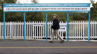 A man walks past the town sign at Llanfairpwllgwyngyllgogerychwyrndrobwllllantysiliogogogoch railway station in Anglesey, Wales, on October 6, 2008. The name of the town is the longest officially recognised place name in the United Kingdom and translated from Welsh means: St Mary's church in the hollow of the white hazel near to the rapid whirlpool and the church of St Tysilio of the red cave. AFP PHOTO/Paul Ellis   / AFP PHOTO / PAUL ELLIS