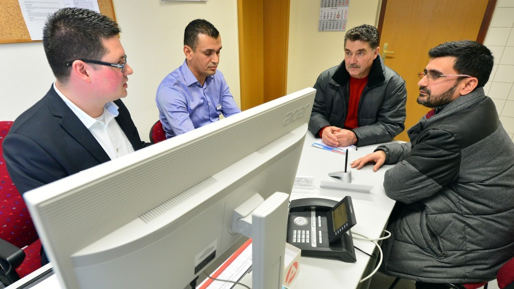 Employment officer Bjoern Oschmann (l-r), assistant Ilyes Benkhouda, Syrian refugee  Salah Kayed and interpreter Keis Al-Zagna sit at a table during a counceling session in a branch office of the 'Bundesagentur fuer Arbeit', the German Federal Employment Agency, at the reception centre for refugees in Muehlhausen, Germany, 22 January 2016. Since the beginning of 2016, the federal agency is recording the educational level and professional skills of arriving refugees to speedup and improve the assessment and placement of refugees in jobs and further education. Photo: Martin Schutt/dpa