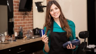 Cute young woman holding a credit card and smiling in a barber shop
