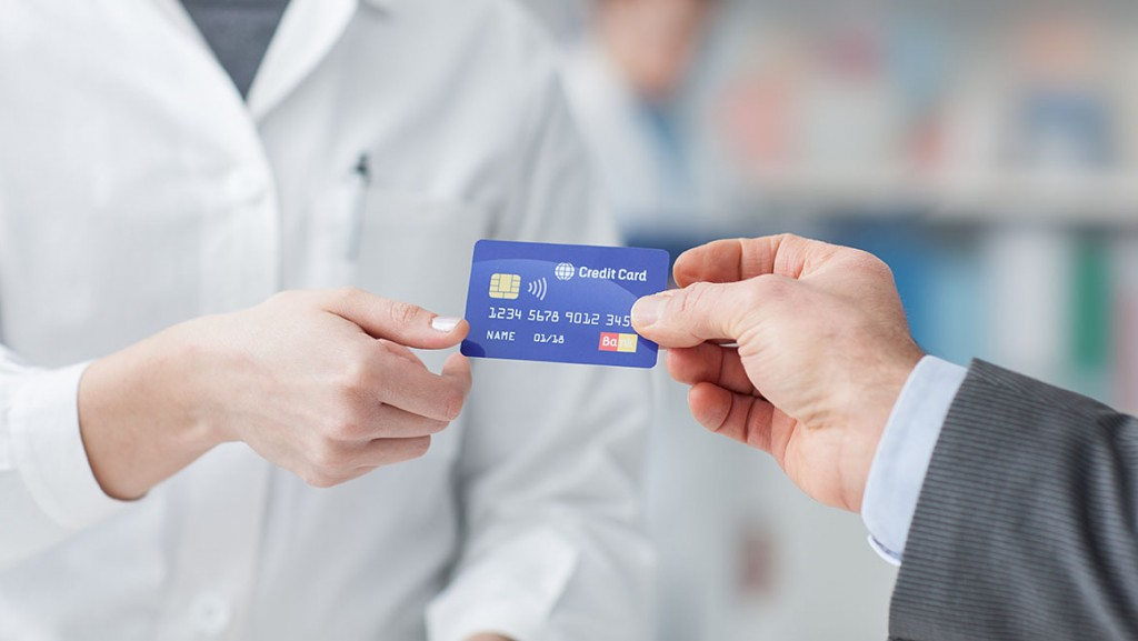 Man at the pharmacy making purchases with a credit card, he is giving the card to the female pharmacist, hands close up