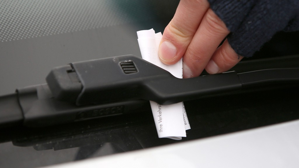 A raffic policewoman issues a parking ticket in Rostock, Germany, 30 January 2015. The city of Rostock has earned more than 1.9 million euro from parking tickets in 2014. Photo: BERND WUESTNECK/dpa