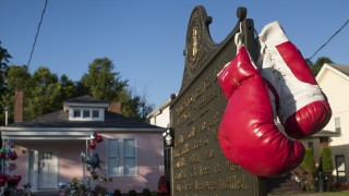 LOUISVILLE, KY - JUNE 10: A pair of boxing gloves hang from a historical marker in front of Muhammad Ali's childhood home on Grand Ave. on June 10, 2016 in Louisville, Kentucky. The funeral procession for Ali will be traveling over 20 miles on a designated route throughout Louisville. The four-time world heavyweight boxing champion died on June 3 at age 74.  (Photo by Ty Wright/Getty Images)