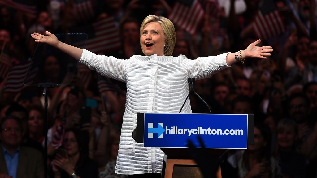 """Democratic presidential candidate Hillary Clinton acknowledges celebratory cheers from the crowd during her primary night event at the Duggal Greenhouse, Brooklyn Navy Yard, June 7, 2016 in New York.  Hillary Clinton hailed a historical """"milestone"""" for women as she claimed victory over rival Bernie Sanders in the Democratic White House nomination race. """"Thanks to you, we've reached a milestone,"""" she told cheering supporters at a rally in New York. """"The first time in our nation's history that a woman will be a major party's nominee.""""  / AFP PHOTO / TIMOTHY A. CLARY"""
