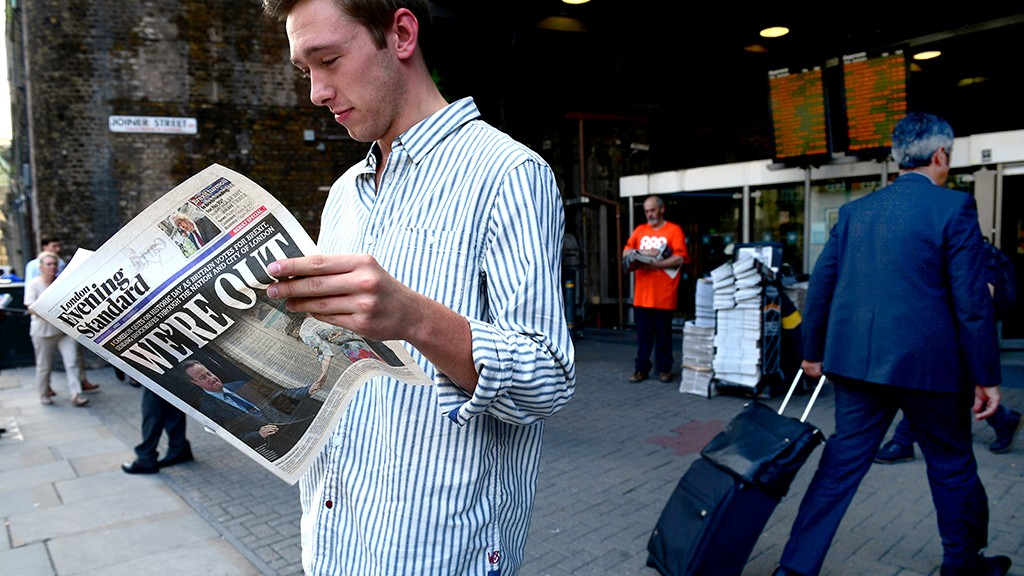 A man reads a copy of the London Evening Standard with the front page reporting the resignation of British Prime Minister David Cameron and the vote to leave the EU in a referendum, showing a pictured of Cameron holding hands with his wife Samantha as they come out from 10 Downing Street, in London on June 24, 2016. Britain voted to break away from the European Union on June 24, toppling Prime Minister David Cameron and dealing a thunderous blow to the 60-year-old bloc that sent world markets plunging. / AFP PHOTO / LEON NEAL