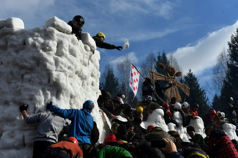 People storm a snow fortress close to the village of Abramtsevo, 60 km north of Moscow on March 13, 2016, in celebration of Maslenitsa (Shrovetide), a farewell ceremony to winter. Shrovetide precedes the beginning of Lent, with each day of the week holding its own meaning. Shrove Sunday, also known as the Sunday of Forgiveness, is a day for asking forgiveness for the harm caused to other people intentionally or unintentionally.  / AFP PHOTO / VASILY MAXIMOV