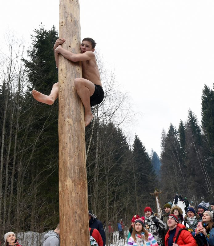 Young man competes in the pole-climb game close to the village of Abramtsevo, 60 km north of Moscow on March 13, 2016, in celebration of Maslenitsa (Shrovetide), a farewell ceremony to winter. Shrovetide precedes the beginning of Lent, with each day of the week holding its own meaning. Shrove Sunday, also known as the Sunday of Forgiveness, is a day for asking forgiveness for the harm caused to other people intentionally or unintentionally.  / AFP PHOTO / VASILY MAXIMOV