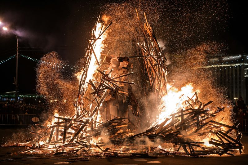 People watch  a berloga («the lair») dummy with 3,5-meter steel bear inside burning down during celebrations  of Maslenitsa (Shrovetide), a farewell ceremony to winter in Moscow's Gorky Park on March 13, 2016. Hungarian artist Gabor Miklos Szoke made a bear as the symbol of spring, and in march it's time to wake him up and get him out of the lair. The art installation consists of two parts: the lair, which will be burnt together with winter and the bear, which will stay at the Park with spring. / AFP PHOTO / DMITRY SEREBRYAKOV