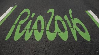 The logo of the Rio 2016 Olympic Games painted in green to distinguish it as the special lane for the games, on a road pedestrianized on Sundays, on June 26, 2016, in Rio de Janeiro, Brazil. / AFP PHOTO / YASUYOSHI CHIBA