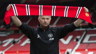 Manchester United's new Portuguese manager Jose Mourinho poses with a scarf on the pitch during a photocall at Old Trafford stadium in Manchester, northern England, on July 5, 2016. Jose Mourinho officially started work as Manchester United manager at the club's Carrington training base yesterday. The 53-year-old was appointed as United boss in May after the sacking of Dutchman Louis van Gaal. / AFP PHOTO / OLI SCARFF