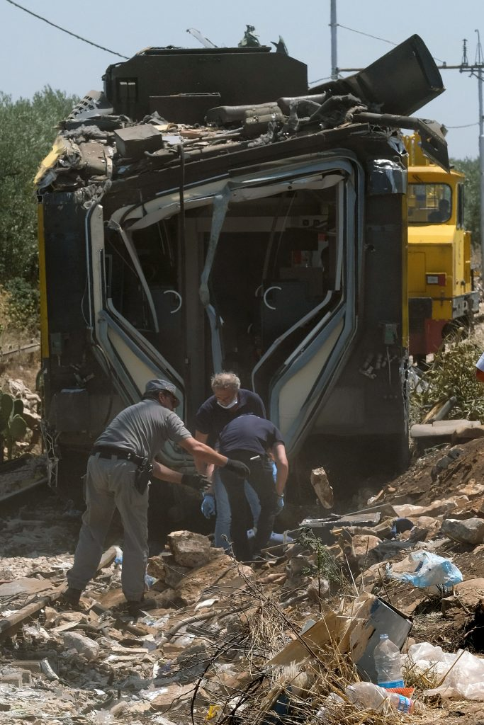 Members of the Italian Dental Division inspect the train crash site on July 13, 2016 near Corato, in the southern Italian region of Puglia  as rescuers searched for missing bodies from the wreckage of a head-on collision that claimed at least 25 lives.     As the country grieved, investigators were trying to establish the cause of the high-speed crash between two busy passenger trains in the Puglia region of southern Italy. The civil protection agency said 25 bodies had been recovered, two people were missing and 50 people had been injured. / AFP PHOTO / MARIO LAPORTA