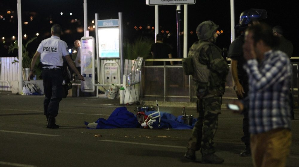 A police officer stands next to a dead body covered with a blue sheet on the Promenade des Anglais seafront in the French Riviera town of Nice on July 15, 2016, after a van drove into a crowd watching a fireworks display. At least 75 people were killed when a truck drove into a crowd watching a fireworks display in the French resort of Nice, a lawmaker said on July 15. / AFP PHOTO / VALERY HACHE